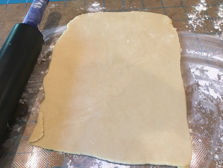 I love using my KitchenAid Gourmet Rolling Pin,  it is wider than most and works like a dream.    The dough does not stick to it if floured.  Here is a photo of a rectangular crust I made for a large Chicken Pot Pie.