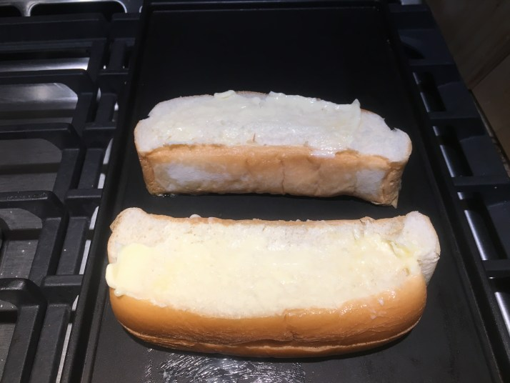 Butter both sides of hot dog rolls and place on a skillet on medium heat.