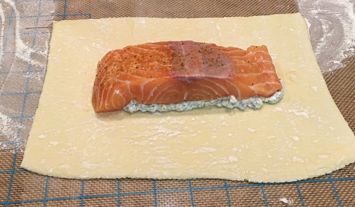 Place 1/2 of the mixture in the center of one piece of the puff pastry and spread it across the dough. Place salmon portion over the mixture.