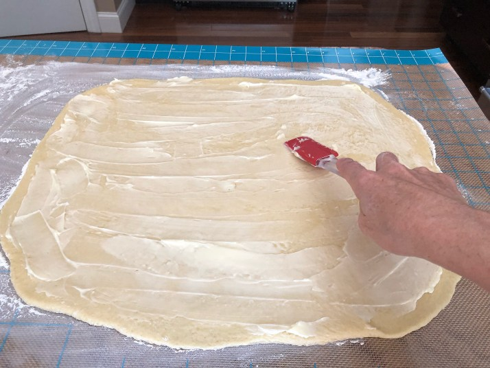 Spread 1/3 cup softened butter or margarine across the entire area of the dough.