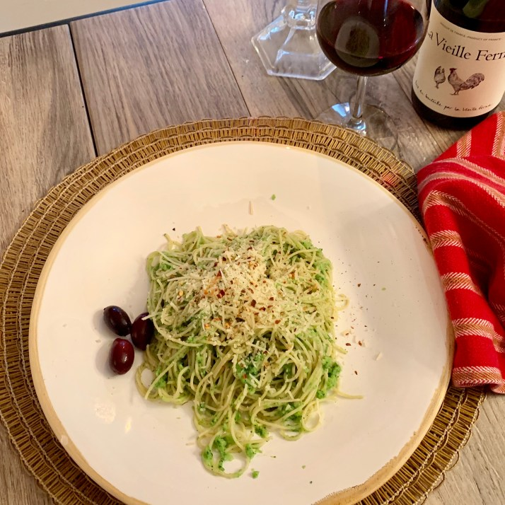 Angel hair pasta with broccoli pesto piled high on a large plate, and a glass of wine . Plate is garnished with three kalamata olives. YUM!