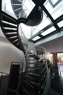 Escalier tournant d'exception sur 4 niveaux, en Inox, acier et pierre naturelle.