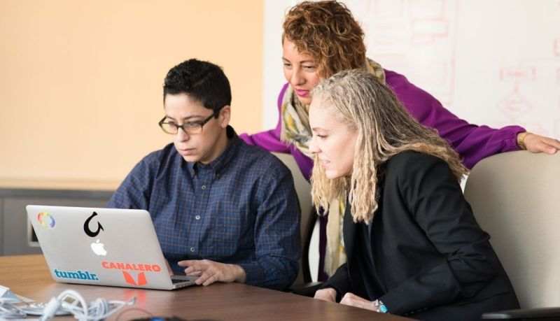 Group Coaching (three people look over a laptop together)