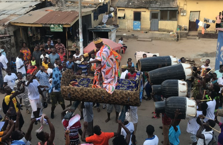At the carnival of the Elmina Bakatue Festival a chief dances in a palanquin held on the heads of men below.