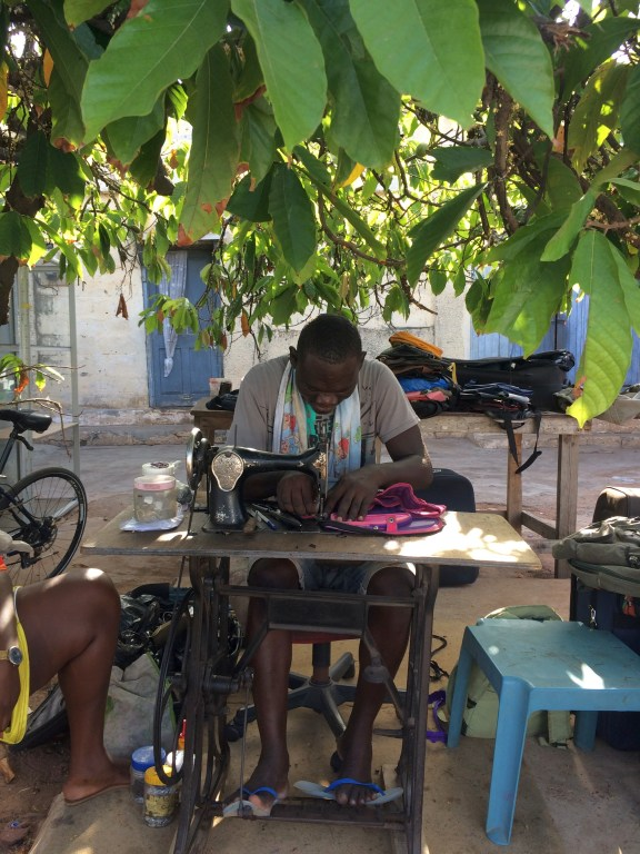A tailor sewing on a pedal powered sewing machine under the trees in Accra Ghana