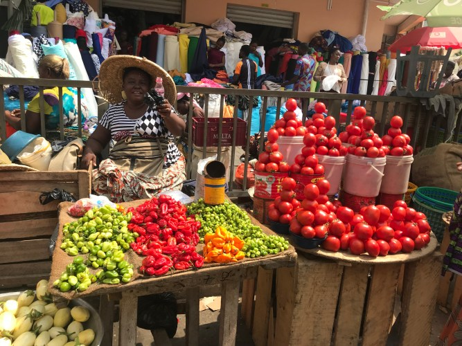 A lady selling tomatoes and local peppers at Makola Market Accra