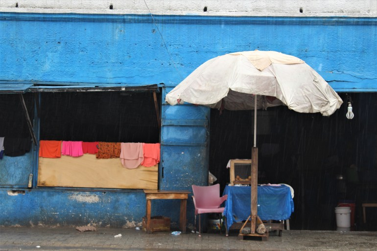 A blue building in old Accra with an umbrella in the front and clothes drying over a wall.