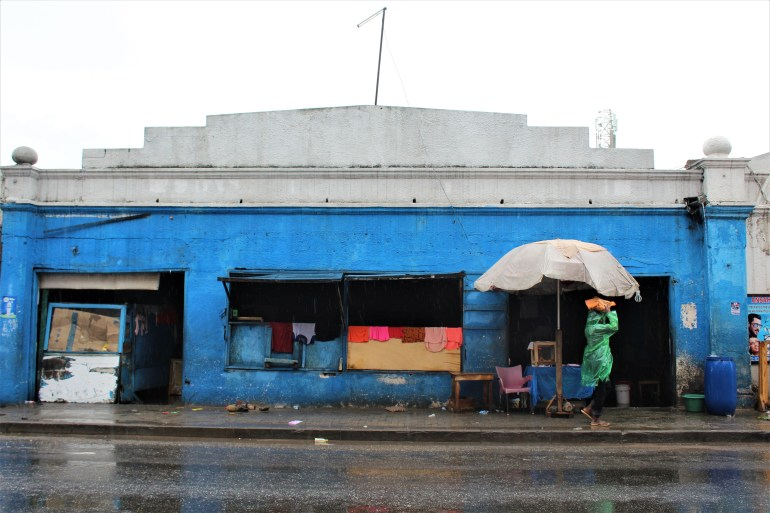 A blue building in old Accra with colourful clothes drying over the walls. It is raining and a person walks past the building in a rain coat.