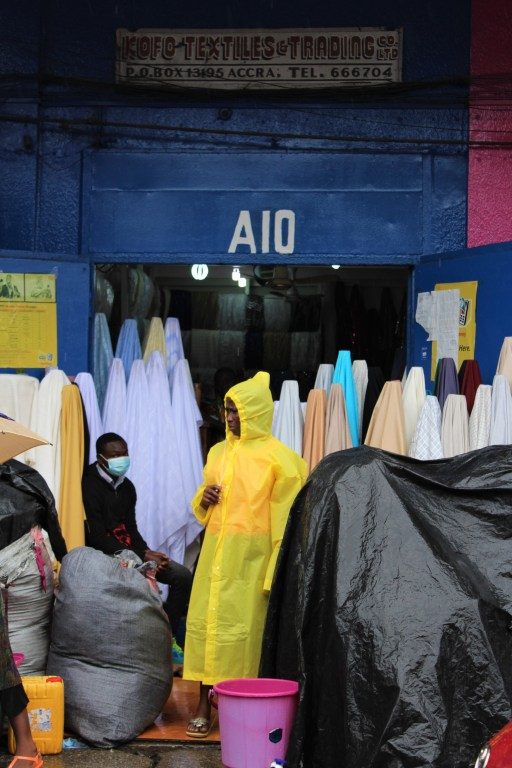 Makola market on a rainy day, A woman stands in a yellow raincoat in front of a store selling fabric marked A10, Kofo Textiles Trading