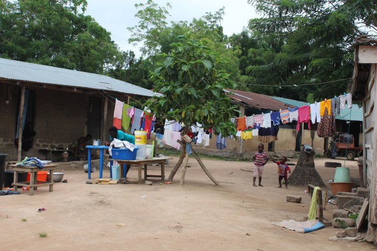 Colourful washing hanging and children playing in a village in Agortime Kpetoe in Ghana