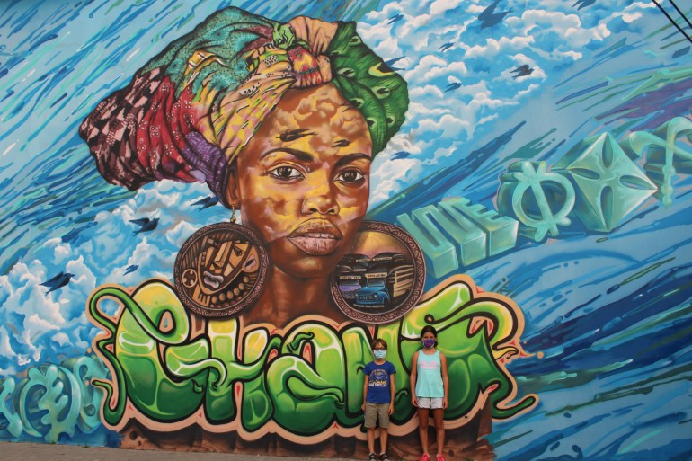 Ghana street art mural depicting a lady with large earrings and Accra street scenes outside Acrilex stationery store in Osu Accra