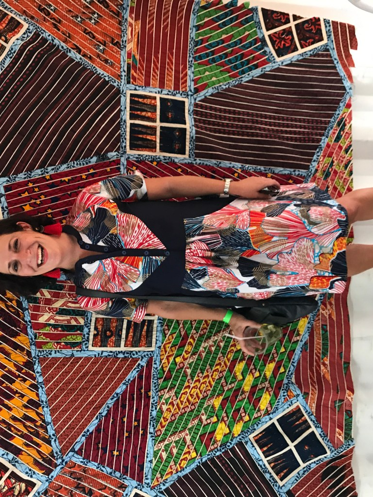 Blogger Lauren Simpson stands in front of Ghanaian artist Tei Huagie's quilts made from African wax fabrics