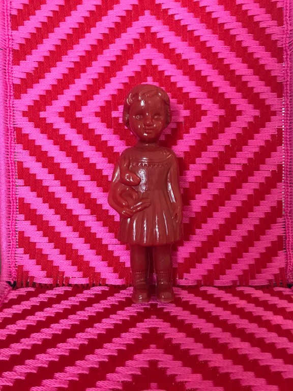 A Red Clonette Doll stands against the backdrop of a woven chair made by Joel at Calao Creation in Ghana