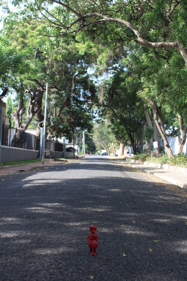 Red Clonette doll stands in a street of Neem trees in Accra Ghana