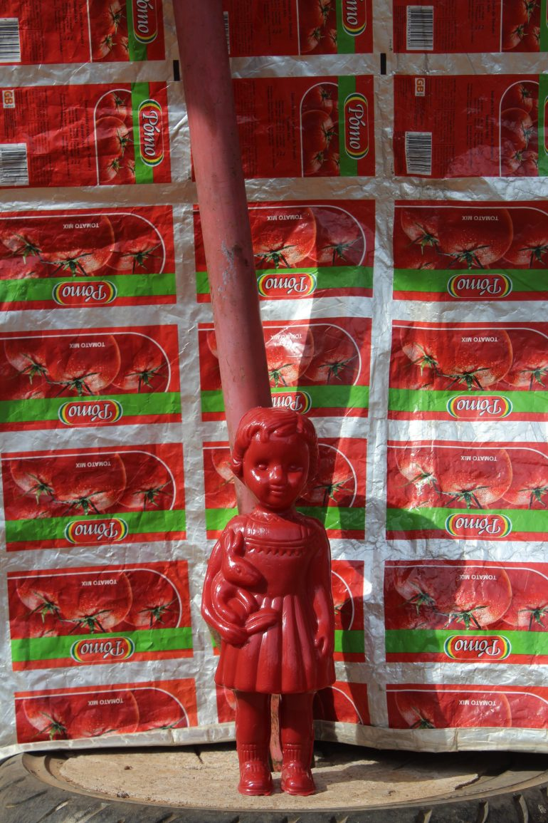 Red Clonette doll in Accra Ghana at a kiosk selling cooldrinks, the labels for tomatoe paste are used as a table cloth.