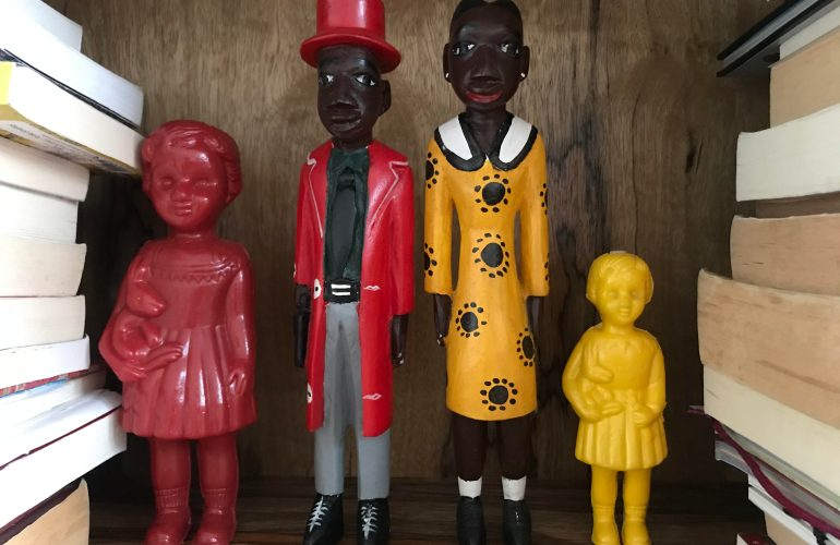 Red and yellow plastic Clonette Dolls stand alongside Ghanaian wooden figures