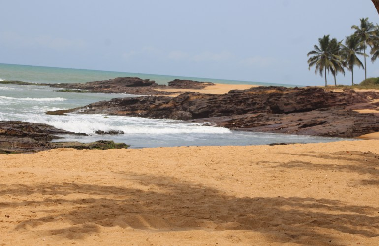 Views of golden sand, gentle waves and palm trees at Ko-Sa beach resort in Ampenyi, Central region of Ghana.