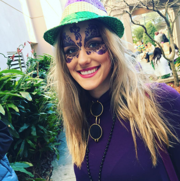 beautiful woman wearing purple flower masquerade mask at mardi gras