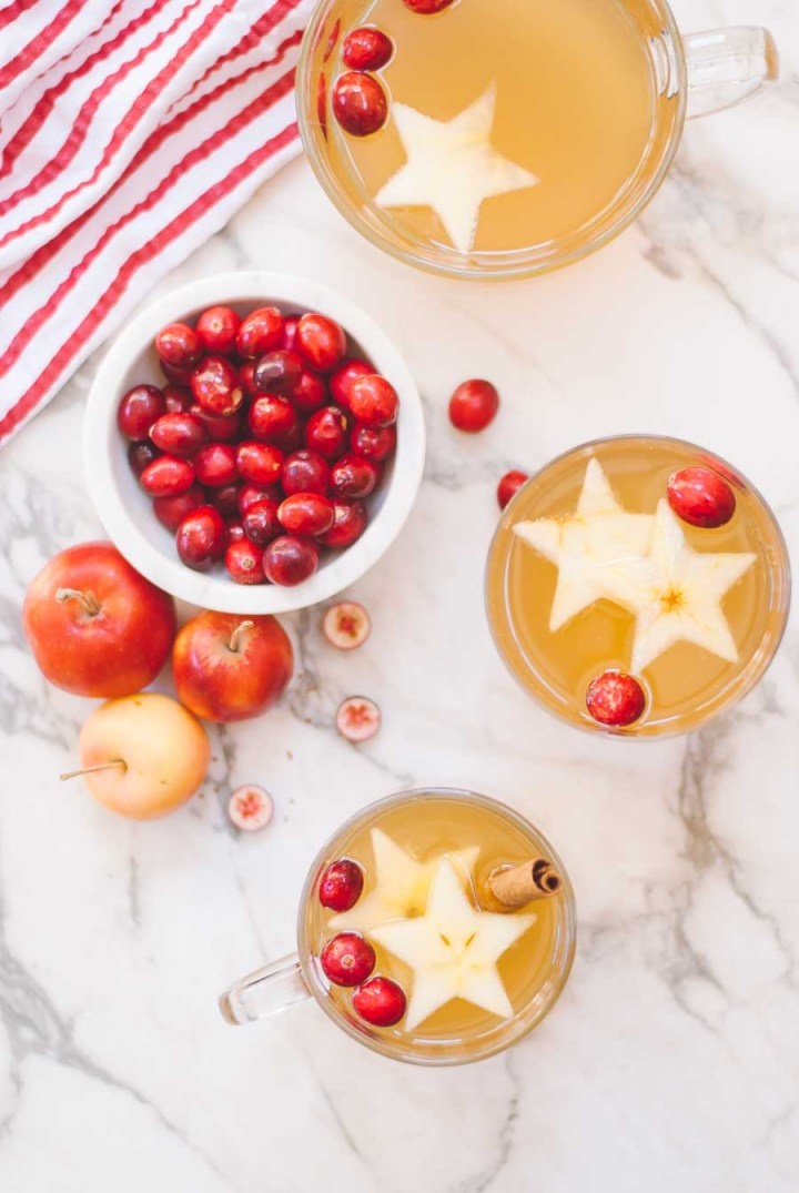 Holiday Cider with star decorations and crab apples and cranberries in a bowl
