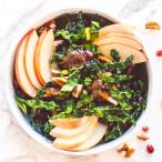 overhead photo of a winter kale salad with an apple butter vinaigrette topped with apple slices, pomegranate seeds, and chopped pecans.