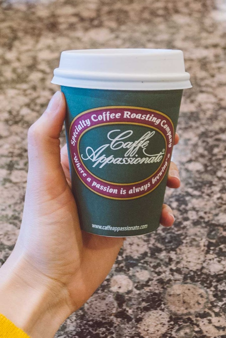 Hand holding a green coffee cup from Caffe Appassionate while on a Seattle coffee tour