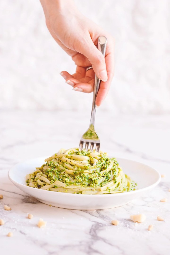 hand with a fork reaching down into lettuce pesto pasta