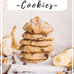 A stack of six cookies on a white board with sliced banana, chocolate chips, and walnuts scattered around the bottom of the picture.
