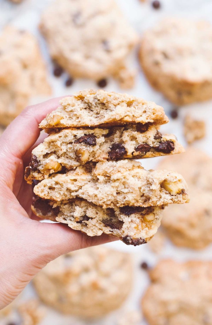 Hand holding a stack of two cookies that have been broken in half so you can see the middle texture of the cookie along with the chocolate chips and walnuts.