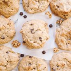 Overhead close up of a single cookie on a square of parchment paper with chocolate chips, walnuts, and other cookies scattered around the center cookie.