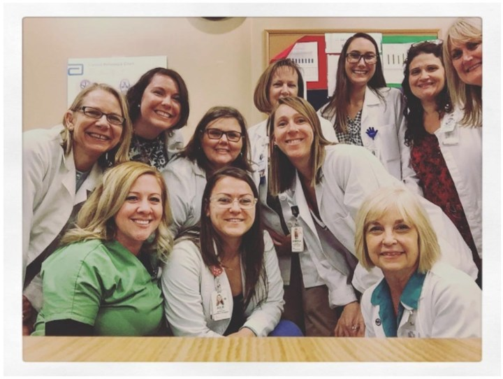 Eleven women wearing white medical coats and scrubs posing and smiling for a picture.
