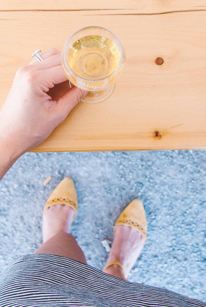 Overhead image of someone holding a glass of icewine resting on a wood table.
