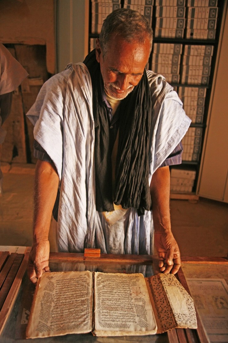 """Man opening a old book in one of the old """"libraries of the desert"""" in Chinguetti"""