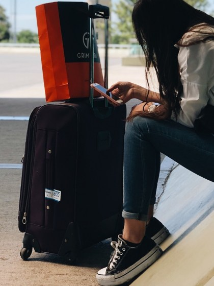 mom-friendly carry-on bags, woman sitting by baggage
