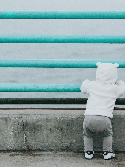 child looking over railing at ocean