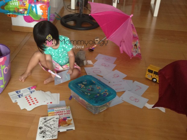Jamie doing her counting and numbering writing at home.  With props.