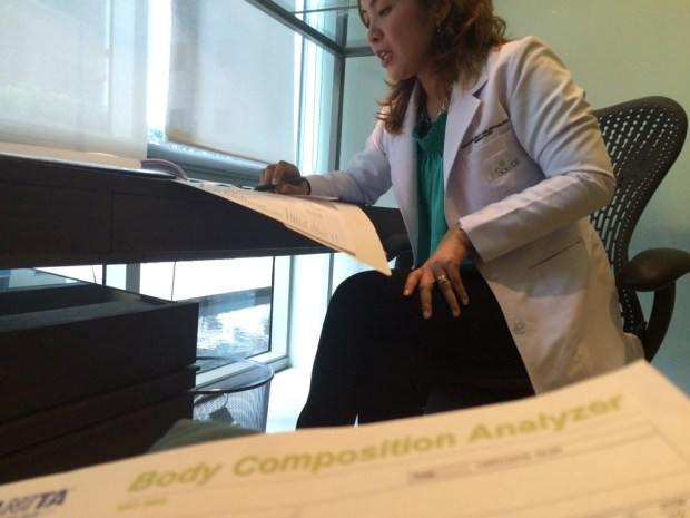 The doctor taking me through my Body Composition Analyzer.