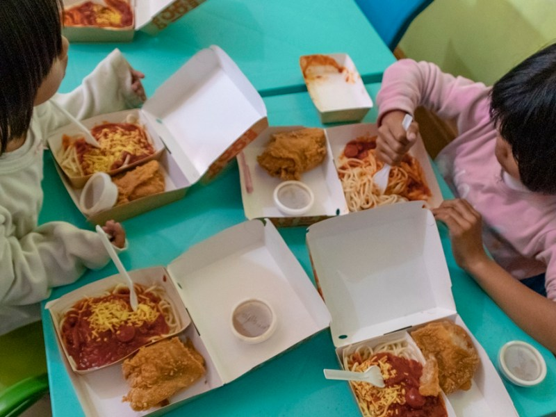 Children eating Jollibee chicken joy and spaghetti