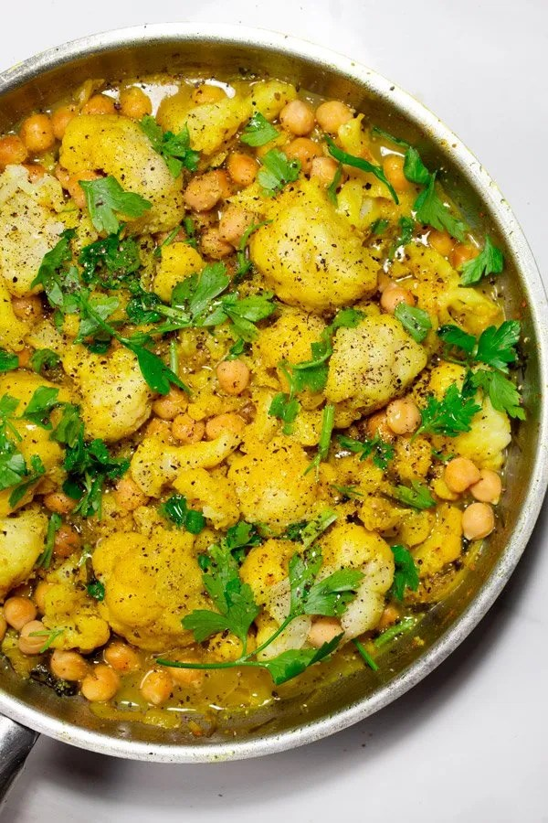 Moroccan Lemon Cauliflower tagine, with chickpeas and fresh parsley in a skillet.