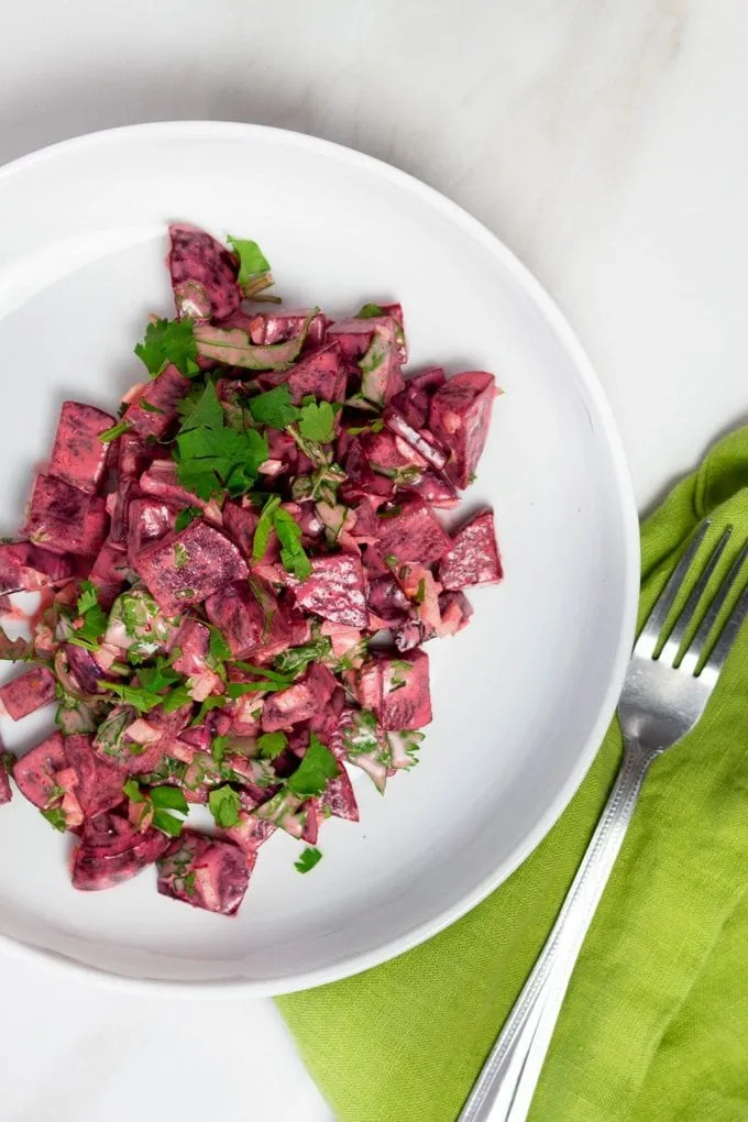 Moroccan Beet Salad served in a white plate and topped with Italian Parsley.