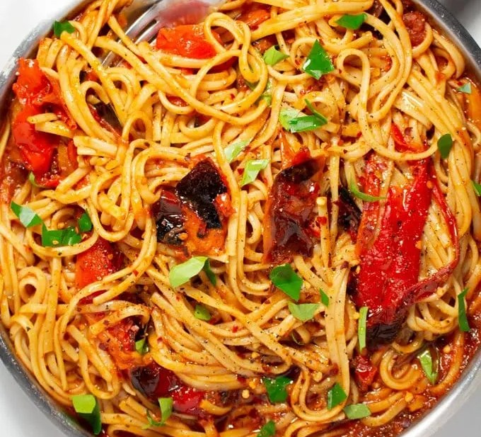 Vegan Moroccan Roasted Red Pepper Pasta served with fresh basil and light drizzle of olive oil. This easy dinner recipe can be made in under 30 minutes!