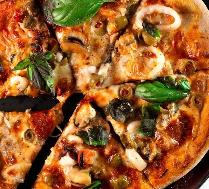 Moroccan Seafood Pizza sliced and served in a cast iron pan