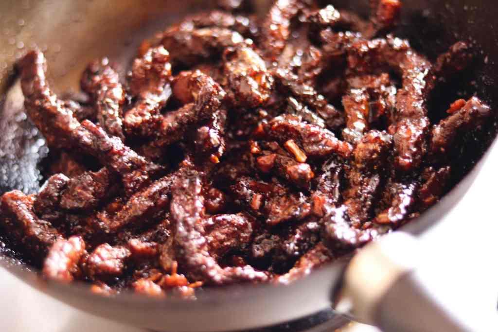 coating crispy beef in sauce.