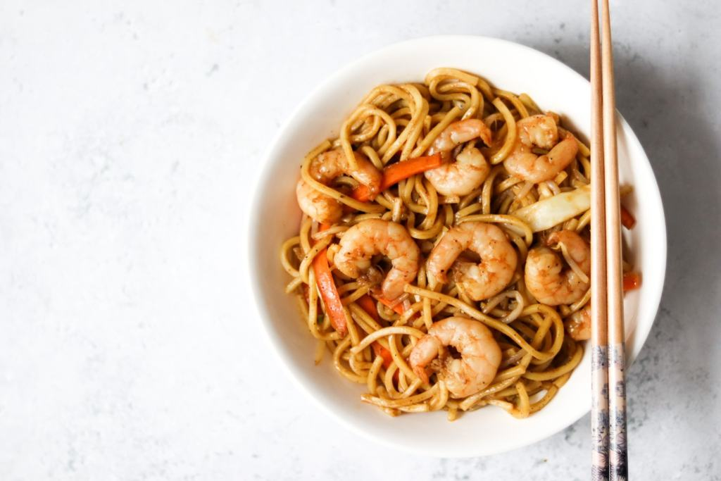 Homemade king prawn chow mein in a bowl with chopsticks.