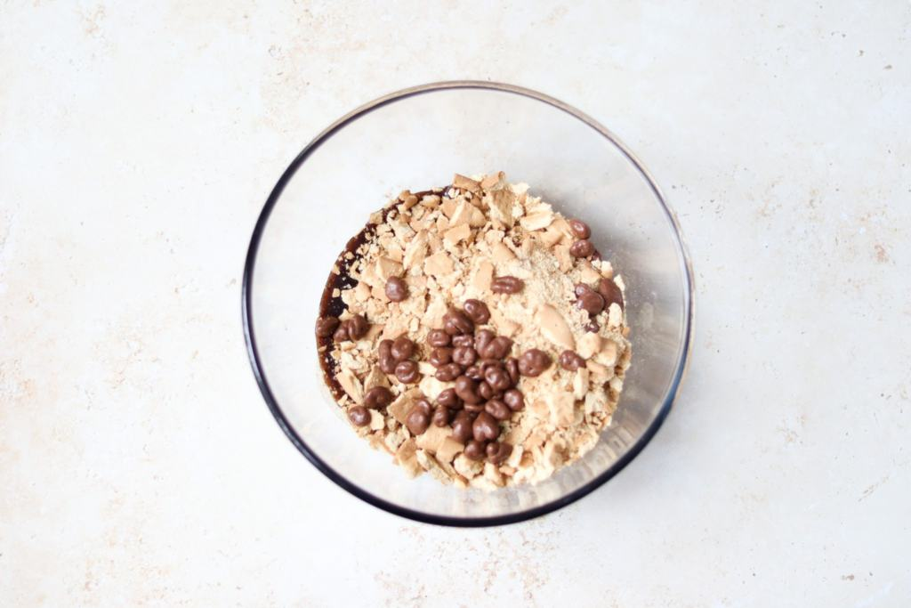 Add crushed biscuits and chocolate raisins to the melted butter mixture.