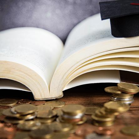Graduation cap, books and money