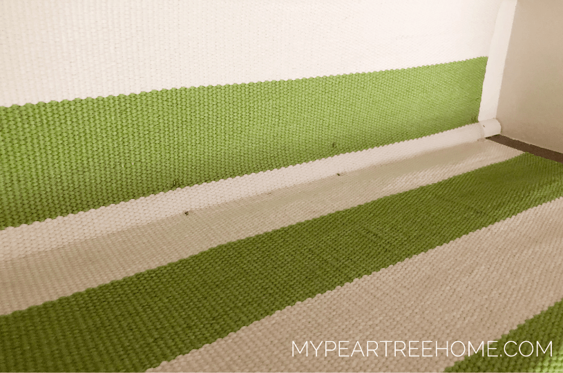 green and ivory stripe carpet stapled on stairs