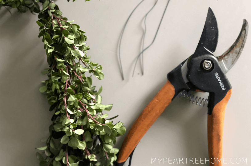 materials needed for making a boxwood wreath (boxwood stems, wire, and clippers)