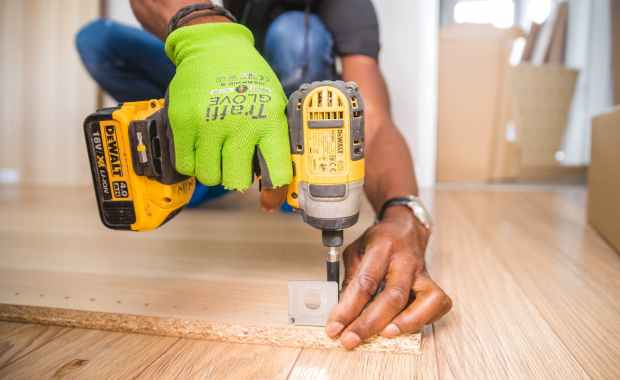 person using dewalt cordless impact driver on brown board