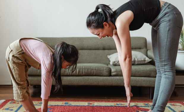 excited barefoot ethnic mother and cute girl doing stretching exercises together