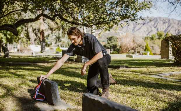 man in black t shirt holding a medal on the graveyard